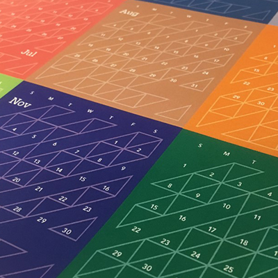 Hub geometric example - Photo of a calendar with different colors for each month with the white outline HUB geometric deign overlay on top.
