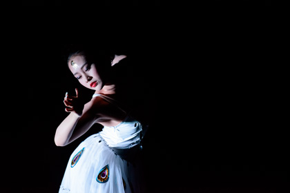 Female Chinese dancer in a white dress with a black background