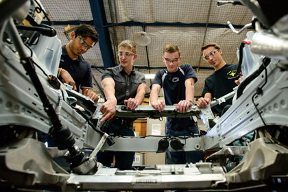 Four male engineering students inspecting the frame of their Eco Car