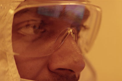 Male researcher face with clear googles and wearing a white coverall on head
