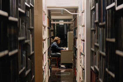 Female student studying at a table and is centered framed in library between aisle of book shelves.