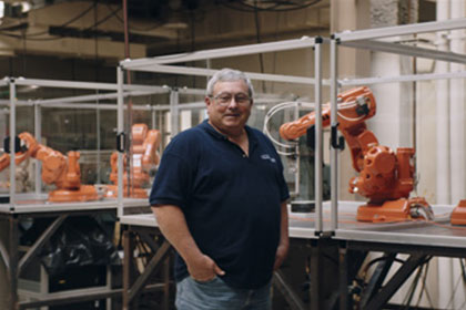 Male professor standing in a shop in front of orange mechanical robotic arms
